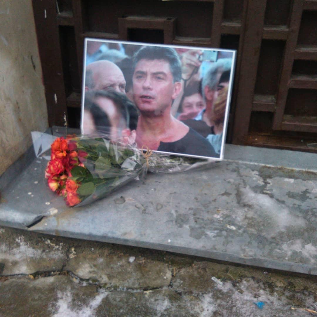 Крупным планом: в нише дома стоит портрет Бориса Немцова на публичном мероприятии в окружении людей.  Перед портретом лежит букет цветов.