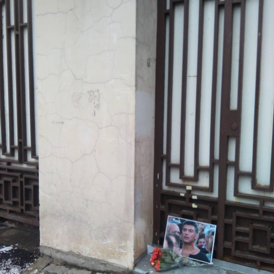 Стена дома.  В нише стоит портрет Бориса Немцова.  Перед портретом лежит букет цветов.