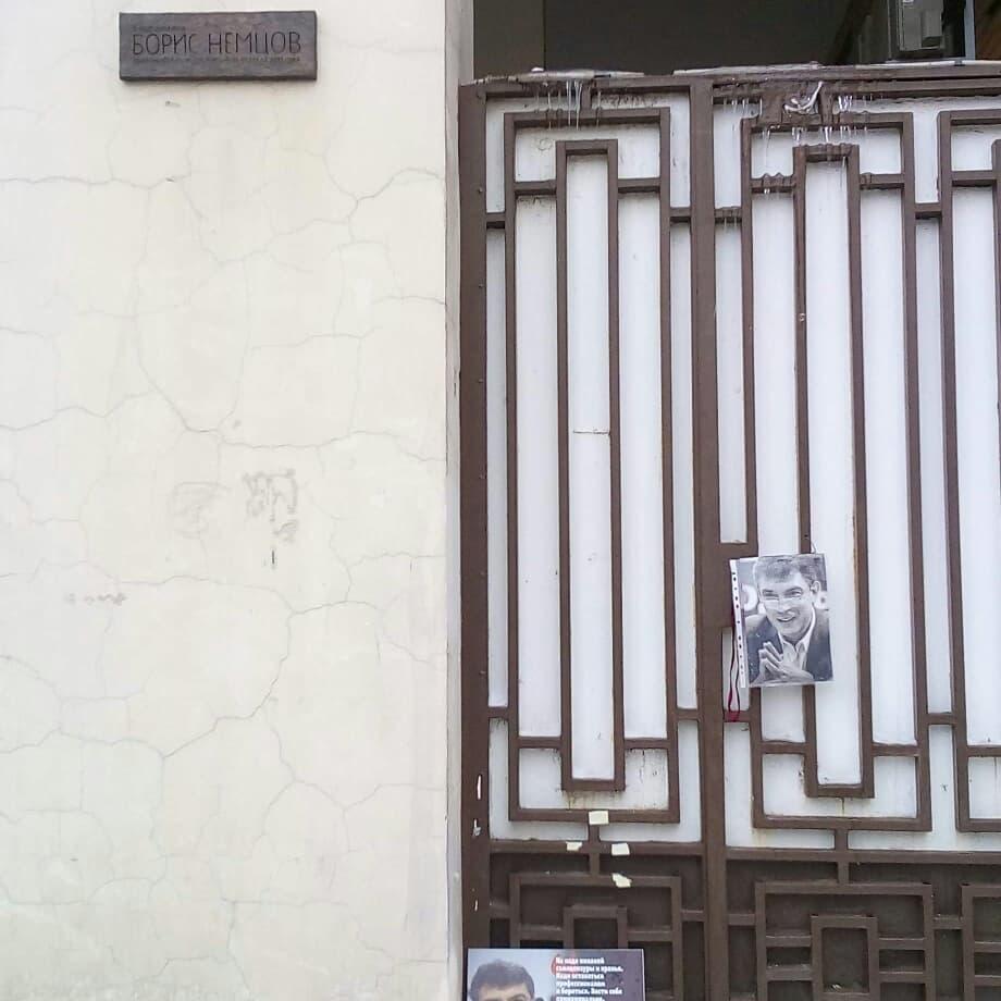Стена дома.  На стене табличка с надписью «В этом доме жил Борис Немцов, выдающийся политик, убитый 27 февраля 2015 года».  Рядом с табличкой металлическая решётка, к которой прикреплён портрет Бориса Немцова.