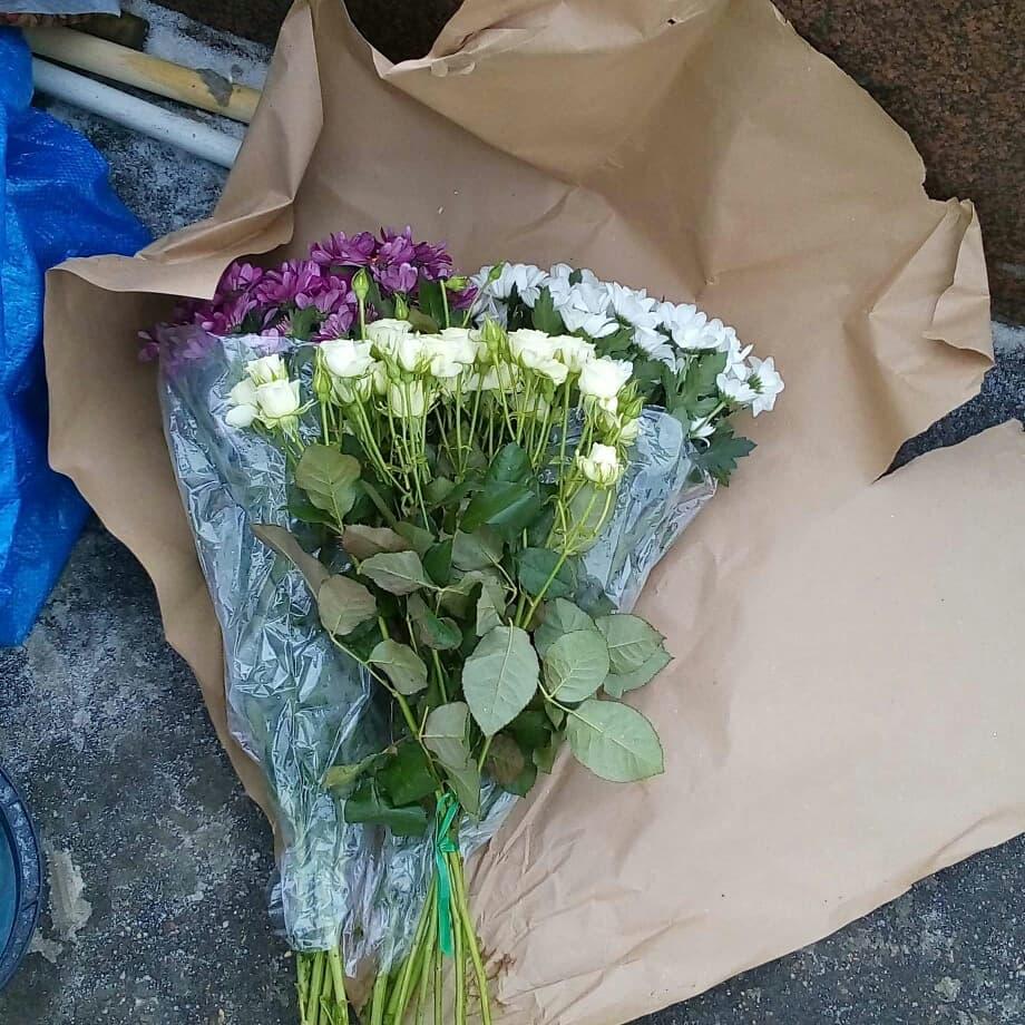 Три букета цветов (два белых и один сиреневый) на оберточной бумаге.