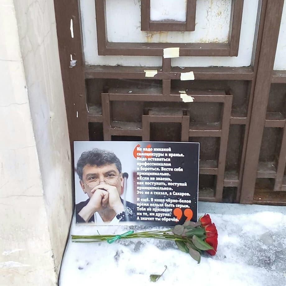 """Ниша в стене дома, где жил Борис Немцов.  Портрет Немцова с цитатой:  «Не надо никакой самоцензуры и вранья. Надо оставаться профессионалом и бороться.  Вести себя принципиально.  """"Если не знаешь, как поступать, поступай принципиально"""".  Это не я сказал, а Сахаров.  И ещё.  В наше чёрно-белое время нельзя быть серым.  Тебя не признают ни те, ни другие.  А значит, ты обречён.»  Перед портретом на снегу цветы."""